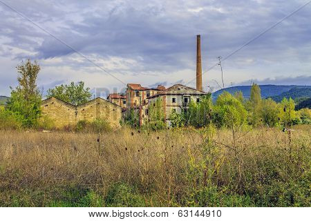 old factory with chimney viewed from afar