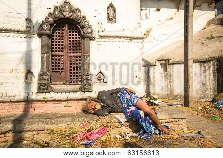 KATHMANDU, NEPAL - DEC 3, 2013: Unidentified local man during the cremation ceremony along the holy Bagmati River in Bhasmeshvar Ghat at Pashupatinath temple in Kathmandu.