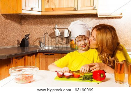 Mother kisses son when he cuts vegetables