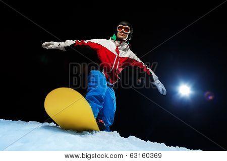 Young man wearing ski mask balancing on snowboard