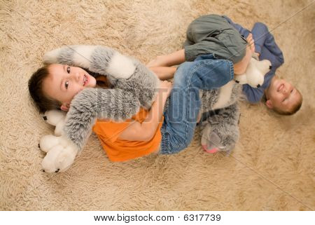Two Kids With A Toy On The Floor