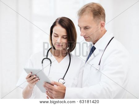 healthcare and medical and technology concept - two doctors looking at tablet pc
