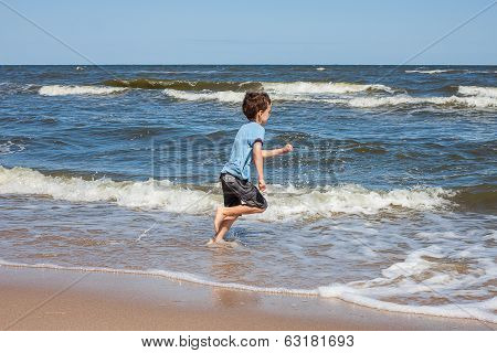 Happy Kid On A Beach