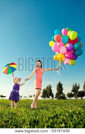 Beautiful little girl with mother colored balloons and rainbow umbrella holding  in  the park. Smiling child and mom on a field with flowers. Kid with mum rest on the  nature. Family outdoor