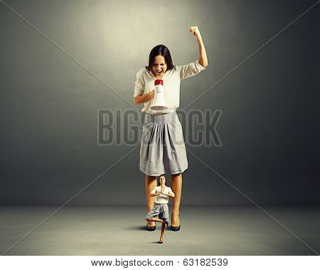 discontented businesswoman screaming at small yoga woman over dark background