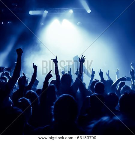 silhouettes of concert crowd in front of bright stage lights, singer on stage