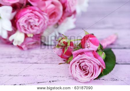 Beautiful wedding bouquet and boutonniere on wooden background