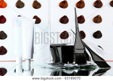 Hair dye kit on board with hair samples of different colors background