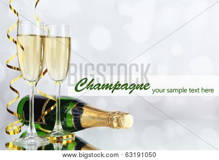 Glasses and bottle of champagne on light background