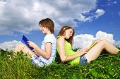 Two girls reading books together outside on grass in summer
