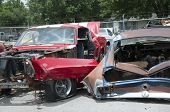 stock photo of junk-yard  - this is a couple of junk yard cars one is red - JPG