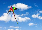 stock photo of kites  - Multicolored kite soars in the sky with clouds - JPG