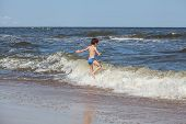image of chase  - Little boy playing at seaside chasing a waves - JPG