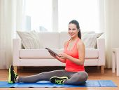 fitness, home, technology and diet concept - smiling teenage girl streching on floor with tablet pc
