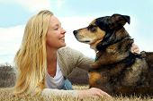 foto of shepherds  - a young caucasian woman is laying outside in the grass with her German Shepherd dog smiling at him - JPG