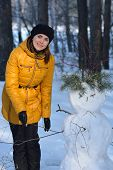 Woman in black beret and a yellow jacket standing next to a snowman.