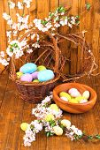 Composition with blooming branches and Easter eggs in wooden bowl, wicker basket on wooden backgroun