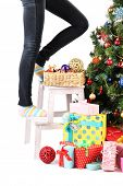 picture of bow-legged  - Female legs on wooden ladder near Christmas tree and gifts isolated on white - JPG