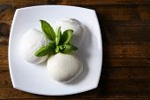 Tasty mozzarella cheese with basil on plate  on wooden background