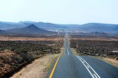 stock photo of paved road  - A paved road over rolling hills in a desert landscape in Namibia - JPG