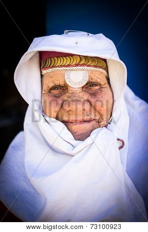 Portrait of very elderly woman wearing golden jewelry under head scarf