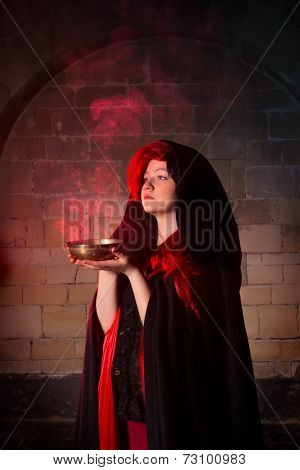 Vampire woman or gothic sorceress with red smoke in a bowl