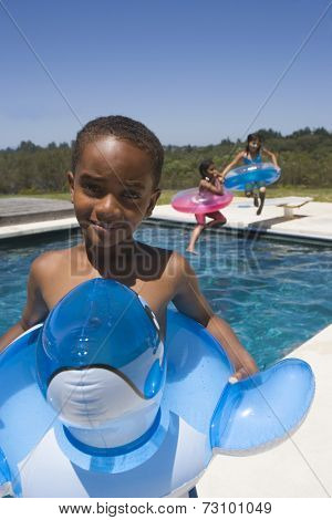 Portrait of boy with innertube at swimming pool