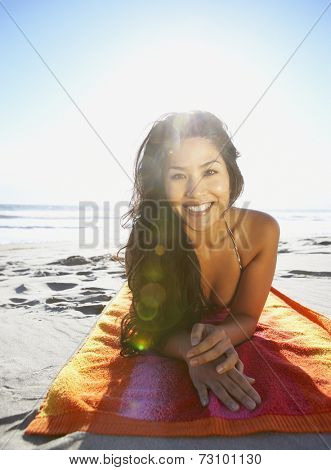 Portrait of woman laying on towel at beach