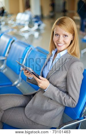 Female employee with touchpad looking at camera while sitting at the airport