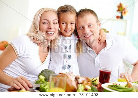 Cheerful couple and their daughter looking at camera at Thanksgiving dinner