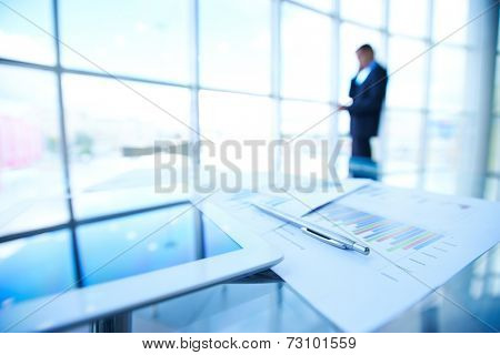 Business documents, touchpad and pen at workplace on background of businessman calling by the window