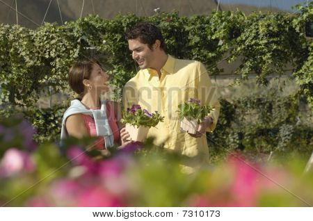 Couple looking at each other and selecting plants at nursery