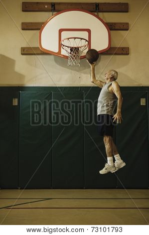 Elderly men jumping to slam dunk a basketball