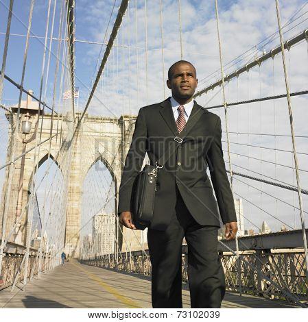 Low angle of businessman walking across bridge