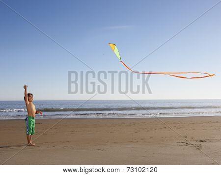 Boy flying kite at beach
