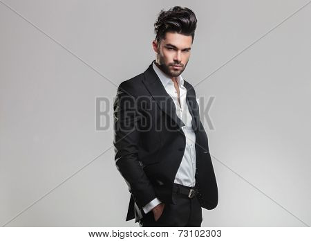 Handsome young man in tuxedo holding his hands in pocket while looking at the camera, on grey background