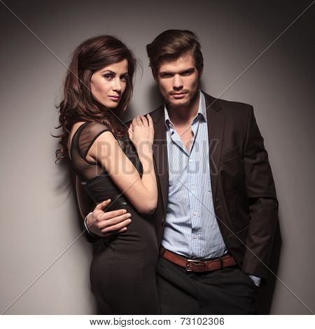 Fashion couple leaning on a dark grey wall looking into the camera. The man is embracing his girlfriend and holding one hand in pocket.