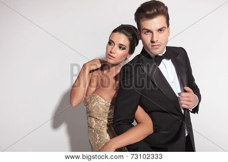 Elegant couple posing for the camera, holding each other arm. The woman is looking away while the man is looking a the camera,