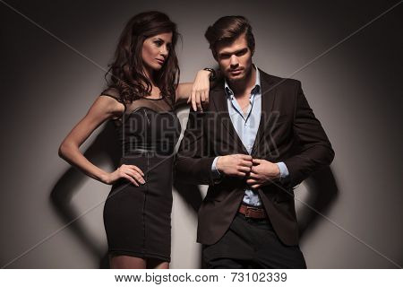 Picture of a elegant fashion couple, the man is unbuttoning his jacket while the woman is looking at him and leaning with one arm. On dark grey background.