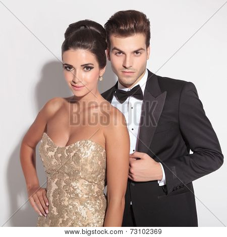 Picture of an elegant couple posing together on studio background, the man is caressing the woman. Looking at the camera.