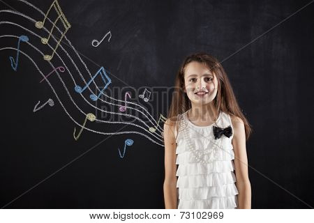 Female child who loves music next to a blackboard