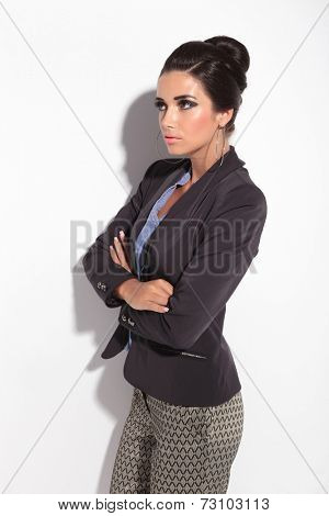 Side view of a sexy business woman holding her arms crossed, looking away from the camera