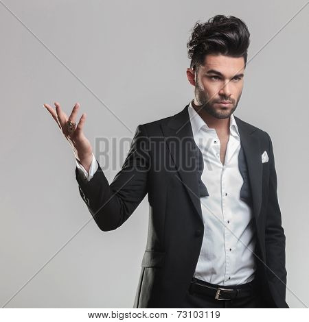 Close up of an elegant young man in tuxedo holding one hand in the air while looking away from the camera. On grey background.