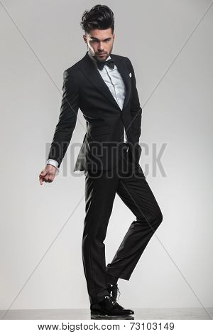Elegant young man in tuxedo looking at the camera while snapping his finger, full body image.