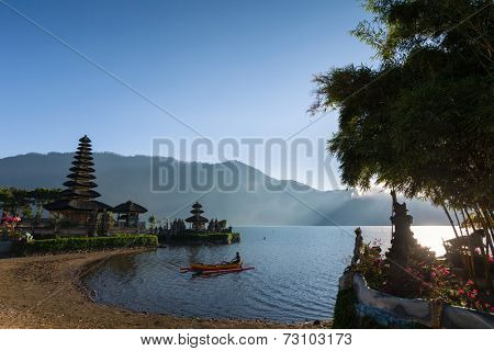 SEPTEMBER 17, 2014 - BALI, INDONESIA: A fisherman rowing a traditional Balinese out-rigger travels across the volcano crater lake of Lake Bratan, Bali Island, Indonesia.