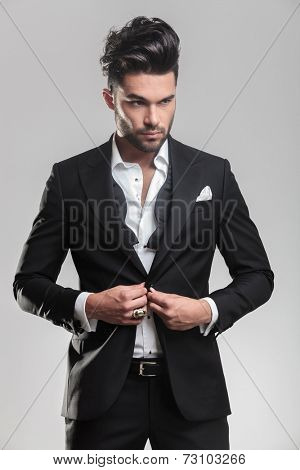 Close up picture of an elegant young man in tuxedo closing his jacket, looking away from the camera. On grey background.