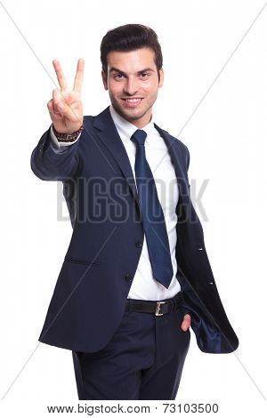 Handsome business man holding one hand in his pocket and showing the victory sign with the other one. On studio background.