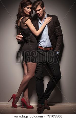 Fulll length picture of a elegant couple embracing. The man is leaning on a dark grey wall with one hand in his pocket.