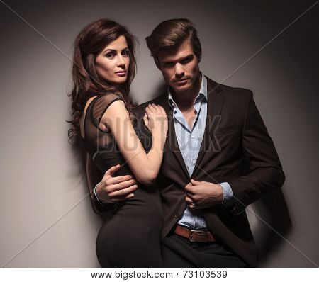 Elegant couple embracing and leaning on a dark grey wall, looking into the camera.