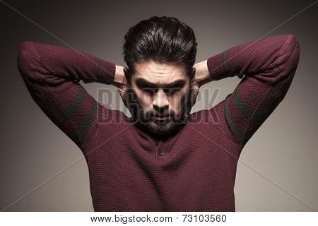 Handsome man in burgundy sweater holding both hands to his neck, looking down